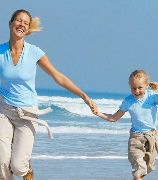 Ouders en kinderen vrolijk rennend op het strand
