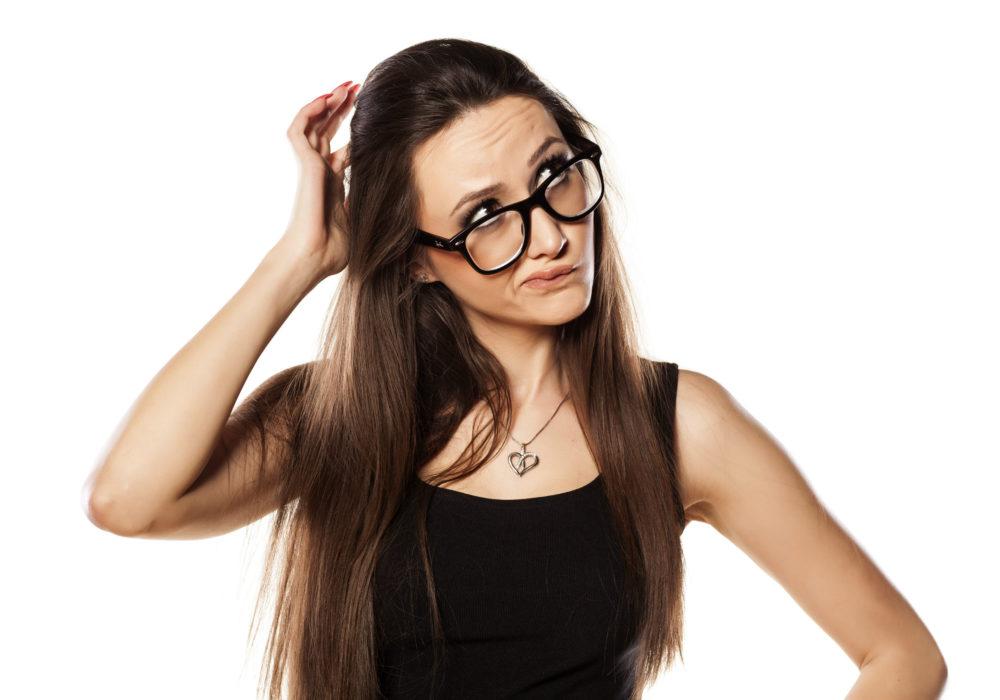 Een jonge vrouw krabbelt in haar haar terwijl ze verward kijkt. Waarheid: Wat is waar?