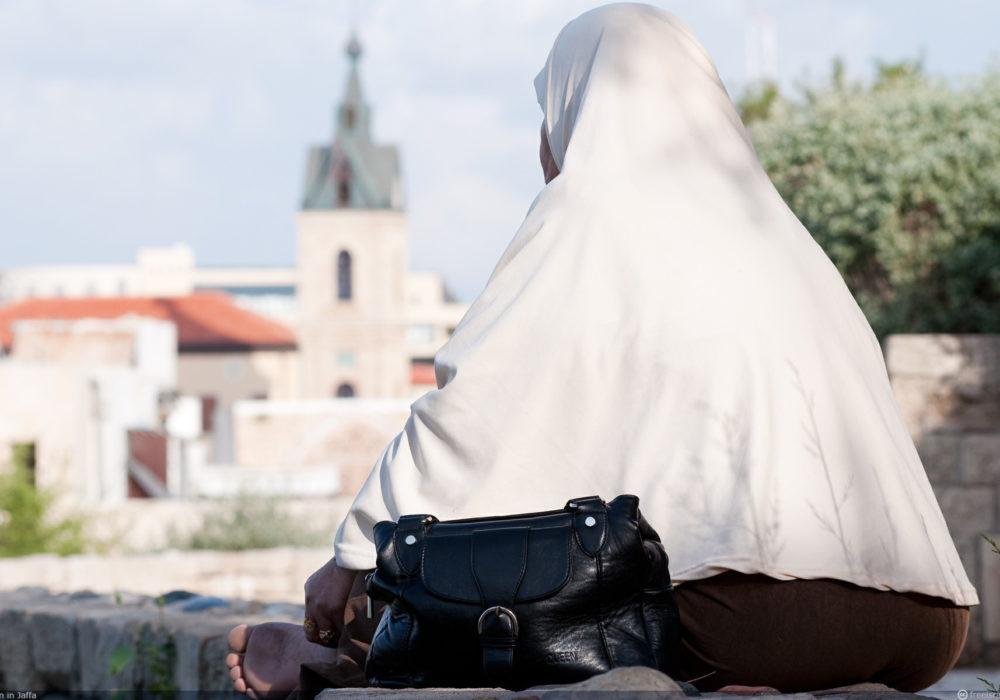 Gesluierde Islamitische vrouw zittend rugzijde. Hoe gaan we om met totaal andere waarden en gebruiken?