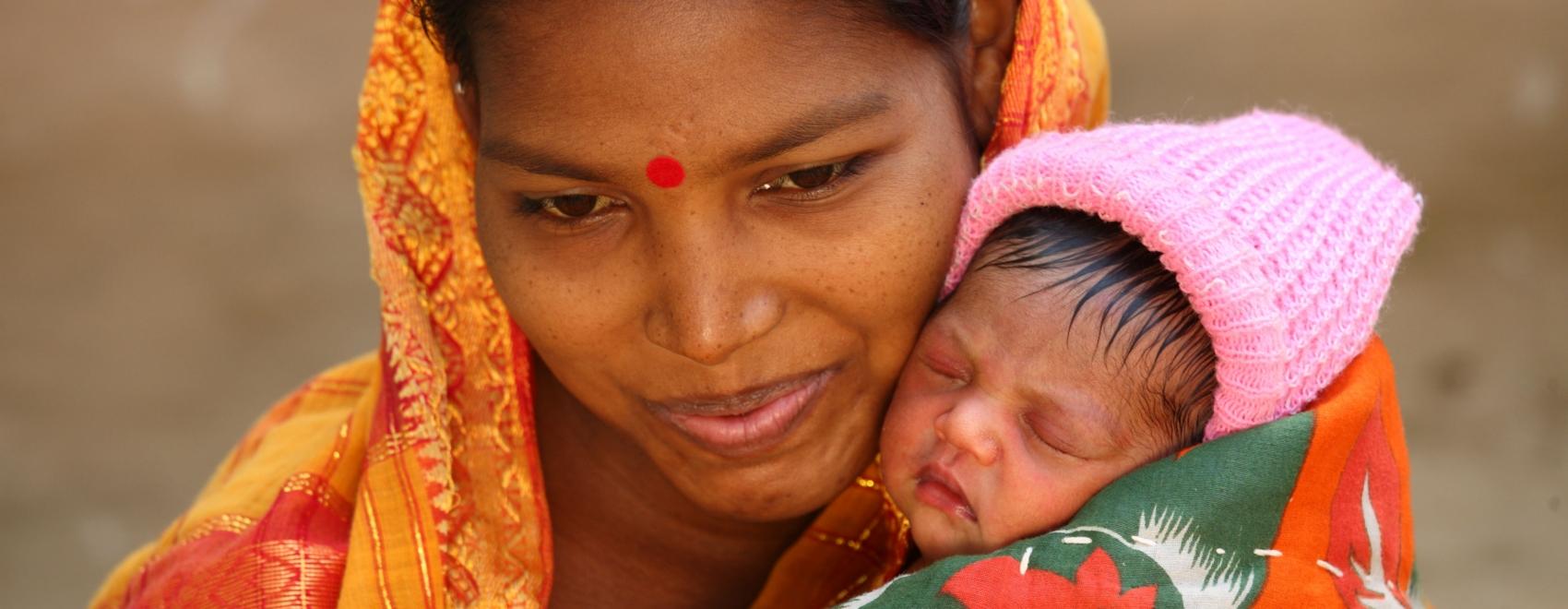 Indiase moeder met baby in oranje omslagdoek. Eindelijk volwassen! Help het kind in je opgroeien naar volwassenheid.