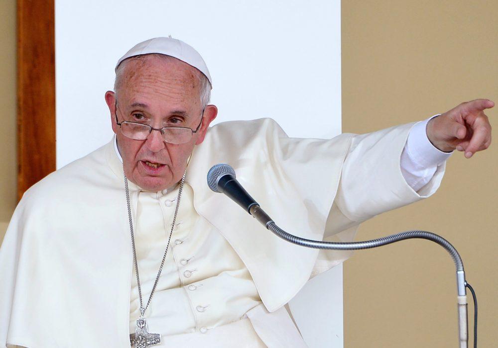 Paus Franciscus wijst alsof hij iemand wegstuurt. Hij vraagt nu vergeving vraagt voor het geweld en de onderdrukking door de Rooms Katholieke Kerk. Het geweld is daarmee nog niet verdwenen. Red God uit de schuld! Geloof, geweld en samen leven