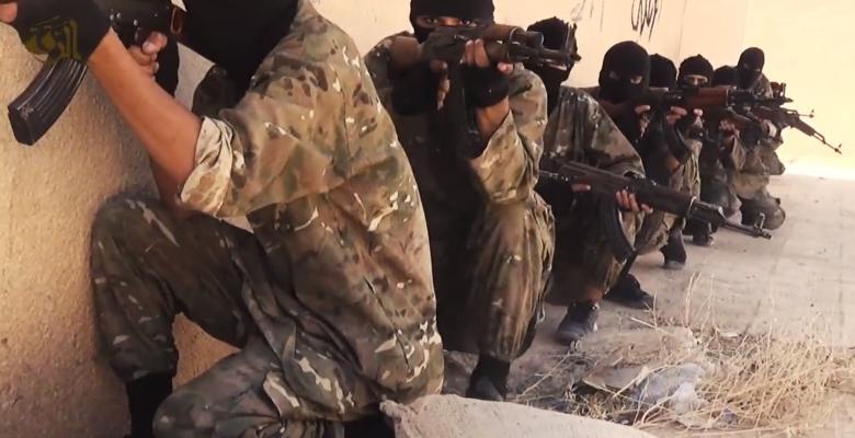 IS strijders in een trainingskamp zitten achter een muur met geweren. Hoe moeten we reageren op terreur, als vrede is wat we willen?