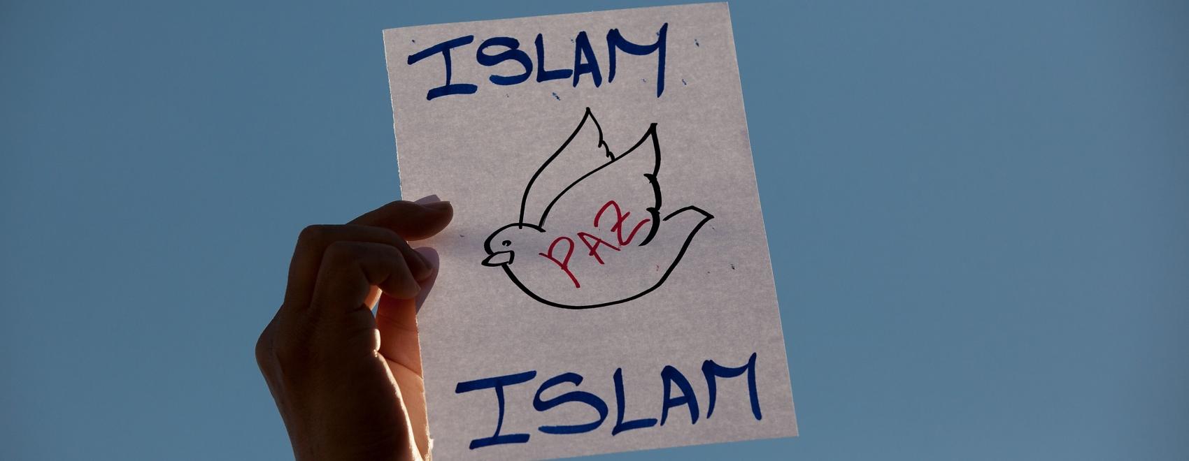 """Betoger houdt na aanslagen het pamflet op me """"Islam Peace"""". Islam staat voor vrede: Kunnen we in vrede samenleven?"""