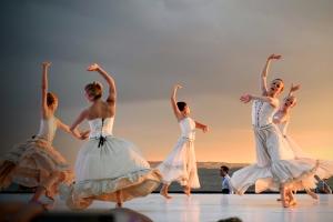 Danseressen in witte jurken dansen sierlijk op een podium buiten
