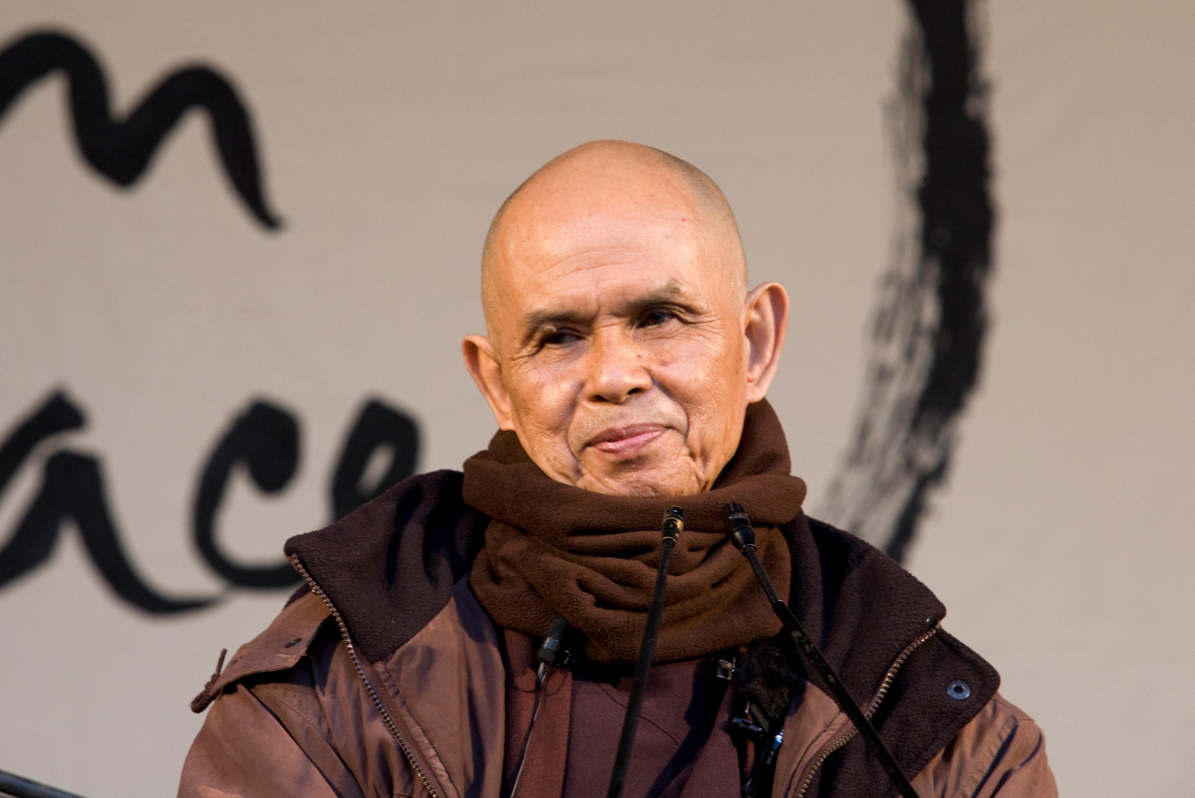 Thich Nhat Hanh warm ingepakt op een podium voor een enorme kalligrafie.