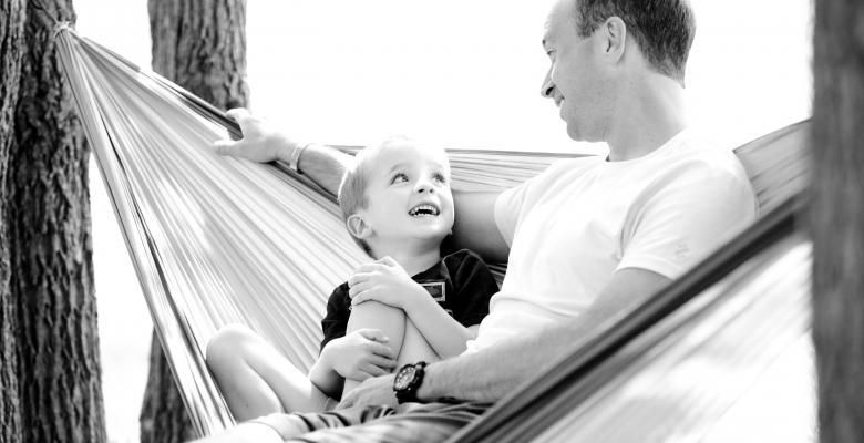 Vader en zoon tijdens een intiem moment in een hangmat