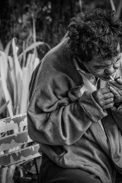 Geven vanuit het hart. Een dakloze op een bank steekt een sigaret op